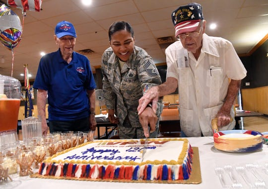 U.S. Air Force Chief MSgt. Adrienne Warren, the youngest member of VFW Post No.  6873, is assisted by Clovis Thompson (right) and Dennis Bruno in cutting a cake Sunday to celebrate the organization's 120th anniversary. Both men served during World War II, Bruno with the Canadian Air Force and Thompson as a U.S. Marine who saw combat in the Pacific.