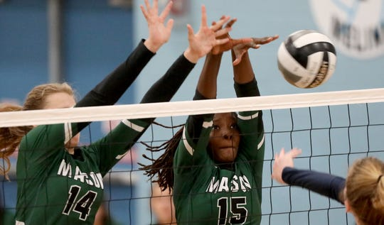 Mason players Chloe Pearce and  Brooklyne Darby block a kill attempt by Mount Notre Dame player Megan Wielonski (12) during theIr volleyball game Saturday, Sept. 28, 2019.