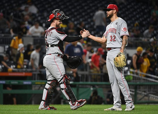 R.J. Alaniz #32 of the Cincinnati Reds celebrates with Tucker Barnhart #16 after the final out in a 4-2 win over the Pittsburgh Pirates in twelve innings at PNC Park on September 28, 2019 in Pittsburgh, Pennsylvania.