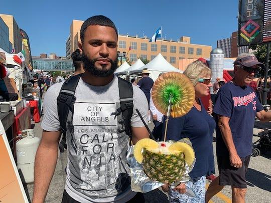 Attendee holding a piña colada from the Caribbean Style Piña Colada vendor.