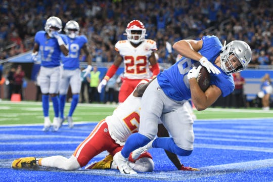 Lions tight end T.J. Hockenson scores a touchdown as Chiefs defensive back Bashaud Breeland attempts to break up the play during the first quarter at Ford Field on Sunday, Sept. 29, 2019.