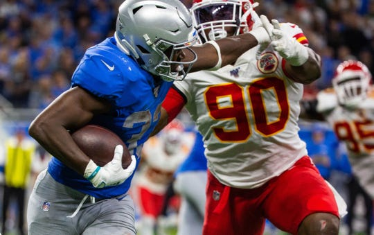 Detroit Lions running back Kerryon Johnson catches a pass and stiff-arms Kansas City Chiefs defensive end Emmanuel Ogbah at Ford Field, Sunday, Sept. 29, 2019. The Lions lost, 34-30.