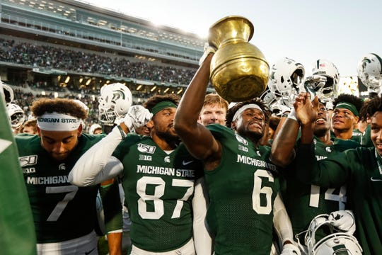 Michigan State safety David Dowell celebrates with the Old Brass Spittoon trophy after the Spartans' 40-31 win over Indiana at Spartan Stadium in East Lansing, Saturday, Sept. 28, 2019.