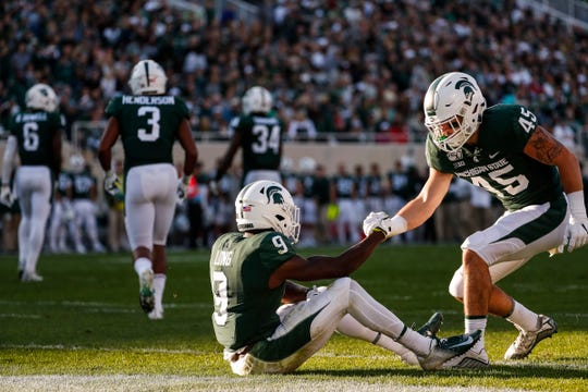 MSU's Dominique Long (9) is helped up by teammate Noah Harvey (45) during the second half vs. Indiana, Sept. 28.