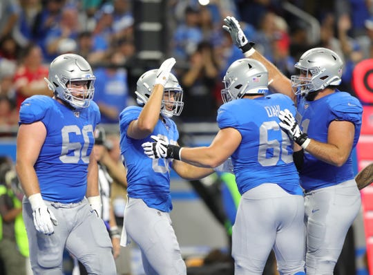T.J. Hockenson, left, celebrates his touchdown with Joe Dahl, center, and Rick Wagner, right, against the Chiefs on Sunday.