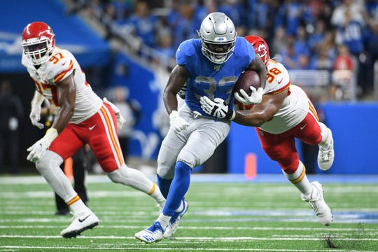 Lions running back Kerryon Johnson is tackled by Chiefs nose tackle Xavier Williams during the second quarter at Ford Field on Sunday, Sept. 29, 2019.