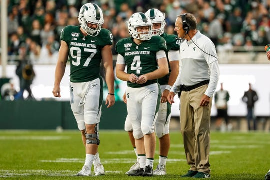 Mark Dantonio talks to kicker Matt Coghlin (4) before his winning field goal attempt during the fourth quarter against Indiana at Spartan Stadium.