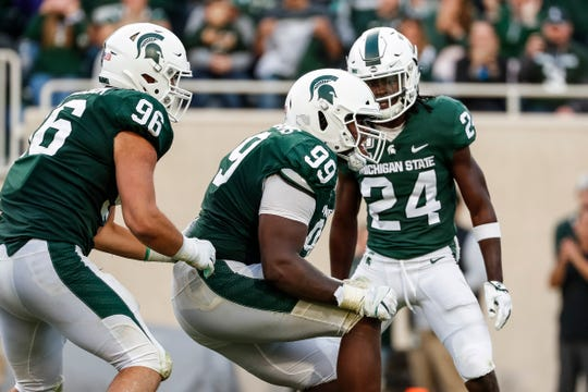 Michigan State defensive tackle Raequan Williams (99) celebrates his sack vs. Indiana with teammates Jacub Panasiuk (96) and cornerback Tre Person (24) during the second half at Spartan Stadium in East Lansing, Saturday, Sept. 28, 2019.