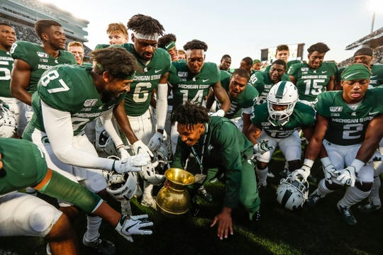 Michigan State cornerback Shakur Brown brings out the Old Brass Spittoon trophy to teammates after the Spartans' 40-31 win over Indiana at Spartan Stadium in East Lansing, Saturday, Sept. 28, 2019.