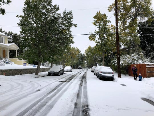 Pedestrians make their way along a snow covered street lined with trees that still have their leaves during a fall snowstorm in Helena, Mont.