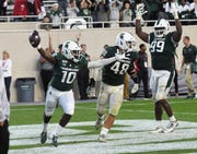 Michigan State's Michael Dowell (10) scores a touchdown on a fumble recovery on the final play of the game and celebrates with Kenny Willekes and Raequan Williams.