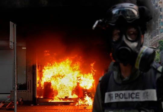 A riot police officer stands next to a subway station which set fire by the protesters at a main street in Hong Kong, Sunday.