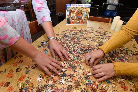 Rabbi Megan Brudney, left, and Laura Williams work on piecing together a puzzle in Temple Beth El's Prentis Memorial Library, which has been transformed into a personal reflection room for the High Holy Days.