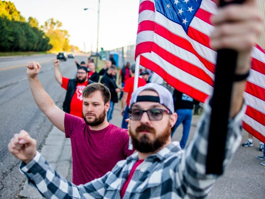 The United Auto Workers strike against General Motors Co. is now in its 16th day. Eric Scharrer, 32, of Davison holds his fist in the air in solidarity while waving an American flag alongside his friend Dell Williston, 32, of Grand Blanc.