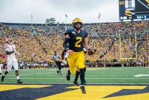 Michigan quarterback Shea Patterson runs the ball for a touchdown in the first quarter.
