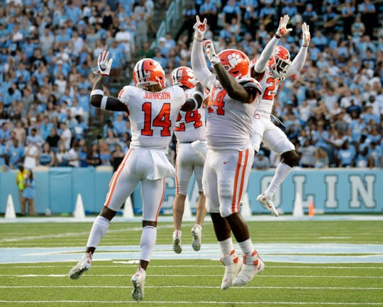 Clemson's Denzel Johnson (14), Nyles Pinckney (44), Nolan Turner (24) and Andrew Booth Jr. (23) celebrate after they stopped North Carolina on a two-point conversion in the closing moments on Saturday.