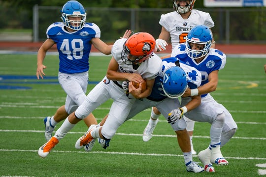 Gregory Piscopink (1) of Brother Rice is tackled in the second half by Mohamed Jaffer (34) and Cody Daraban (22) of Catholic Central on Sunday.