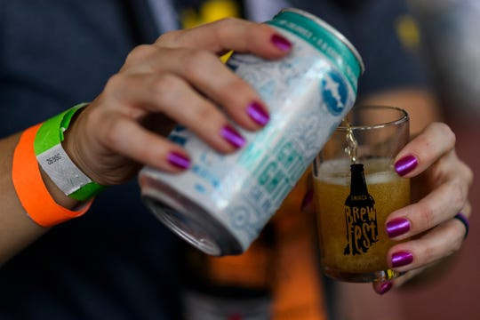 Gina Downs serves up a Slightly Mighty Lo-Cal India Pale Ale at the Dogfish Head Craft Brewery tent during the 16th annual SWIRCA Brewfest at Bosse Field in Evansville, Ind., Saturday, Sept. 28, 2019.