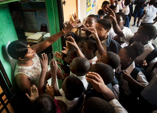 Mona Lisa Forbes hands out lunch tickets to students at Anatol Rodgers High School in Nassau, Bahamas on Wednesday, September, 25, 20019. The school has taken in a large number of students from the Abaco and Grand Bahama Islands that were displaced due to Hurricane Dorian.