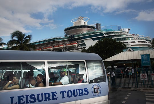 A bus transports cruise tourists from the boat docks to downtown Nassau, Bahamas three weeks after Hurricane Dorian.