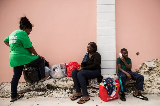 From left, Hurricane Dorian survivors and Marsh Harbour residents,  Islane Pierre, Keri Pierre, and Carlito Forbes take a break in front of the Comfort Inn and Suites on Paradise Island in Nassau, Bahamas on Monday, September 23, 2019. They were walking with donated supplies from the Salvation Army. They have been staying in a hotel on Paradise Island in Nassau for several weeks, but that is about to expire. After that, they don't know where they will go.