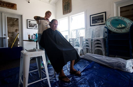 Hairdresser, Tabitha Wallace cuts the hair of Great Guana Cay resident, Philip Bethel on  Man O War Cay in the Bahamas on Wednesday, September 25, 2019. The island was heavily damaged in Hurricane Dorian three weeks earlier. She was providing services for people still living on the island. Great Guana Cay also sustained heavy damage from Category 5 storm.