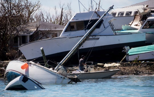 A boater moves through heavily damaged boats across from Man-O-War Cay in the Bahamas on Wednesday, September 25, 2019. The island was heavily damaged in Hurricane Dorian three weeks earlier.