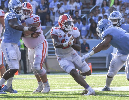 Clemson running back Travis Etienne (9) runs near the blocking of teammate offensive lineman Gage Cervenka (59) during the second quarter  at Kenan Memorial Stadium in Chapel Hill, North Carolina Saturday, September 28, 2019.