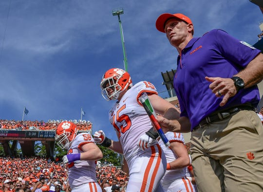 Clemson Defensive Coordinator Brent Venables and his son Jake run on the field before the game with North Carolina at Kenan Memorial Stadium in Chapel Hill, North Carolina Saturday, September 28, 2019.