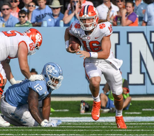 Clemson quarterback Trevor Lawrence (16) runs with the ball against North Carolina during the second quarter  at Kenan Memorial Stadium in Chapel Hill, North Carolina Saturday, September 28, 2019.