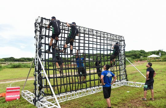 Variety Pack team members climb the cargo net wall obstacle during Trench Challenge 2019 at the Guam International Raceway in Yigo in this Sept. 29, 2019, file photo.