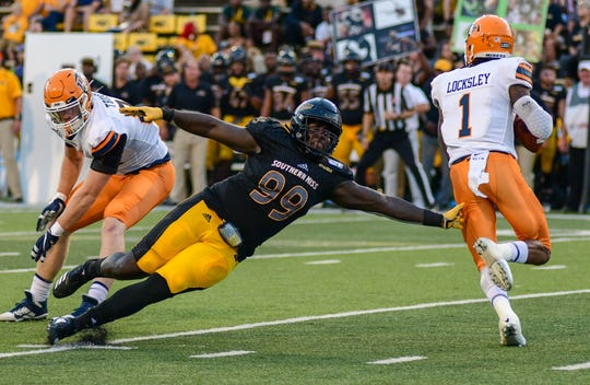 Southern Miss Golden Eagles defensive line Jacques Turner tries to tackle UTEP Miners quarterback Kai Locksley Sept. 28, 2019.