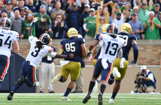 Fighting Irish defensive lineman Myron Tagovailoa-Amosa (95) is tackled by Virginia Cavaliers quarterback Bryce Perkins (3) after he recovered a Perkins fumble in the third quarter at Notre Dame Stadium.