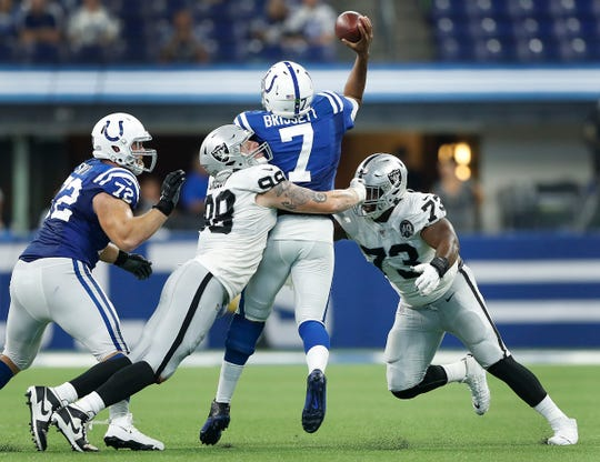 Indianapolis Colts quarterback Jacoby Brissett (7) is pressured by Oakland Raiders defensive end Maxx Crosby (98) and Maurice Hurst (73) late in the fourth quarter of their game at Lucas Oil Stadium on Sunday, Sept. 29, 2019. The Colts lost to the Raiders 31-24.