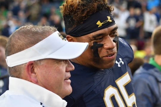 Fighting Irish head coach Brian Kelly and defensive lineman Myron Tagovailoa-Amosa (95) leave the field after Notre Dame defeated the Virginia Cavaliers at Notre Dame Stadium.