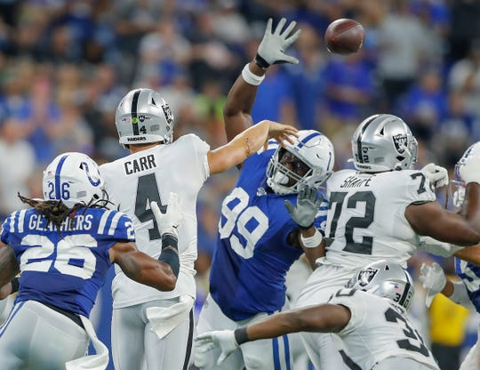 Oakland Raiders quarterback Derek Carr (4) gets the pass away as Indianapolis Colts defensive end Justin Houston (99) defends in the second half of their game at Lucas Oil Stadium on Sunday, Sept. 29, 2019. The Colts lost to the Raiders 31-24.