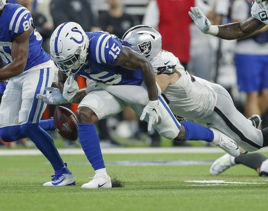 Indianapolis Colts wide receiver Parris Campbell (15) fumbles the ball after he is hit by Oakland Raiders defensive end Maxx Crosby (98) in the first half of their game at Lucas Oil Stadium on Sunday, Sept. 29, 2019.