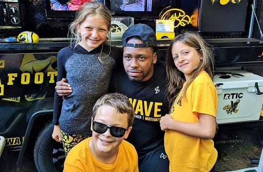 Hawkeye great Akrum Wadley signed the Smith trailer last year and had a chance to meet Bailey (left) and Chloe Madura, plus Carter Smith in front.