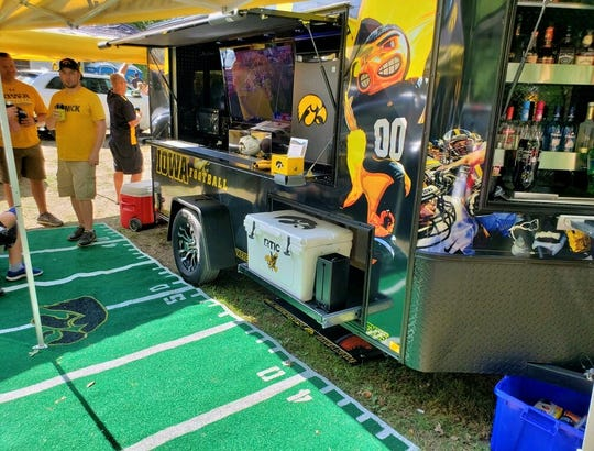 The entertainment center side of the trailer offers a big-screen TV, refrigerator, microwave oven, pull-out cooler drawer and bar, plus an artificial grass rug depicting a football field.