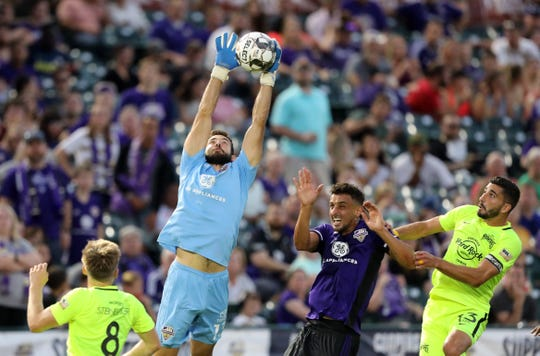 Louisville City FC's goal keeper Chris Hubbard (13) fights for the ball under pressure from the Tampa Bay Rowdies during their game at Slugger Field in Louisville, Ky.  Sept. 28,  2019.