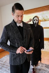 "Century 21 Realtor James Pyle is happy with the response of people viewing his Zillow listing for a house at 809 Chestnut Street in Lansing, which includes friend Andrew Lamkin dressed as the ""Scream"" character, Ghostface, Sunday, Sept. 29, 2019. Here, he checks his Zillow listing which has nearly 300,000 views since he included the Ghostface character in his photos."