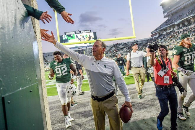 Michigan State coach Mark Dantonio slaps hands with fans after MSU's win over Indiana on Sept. 28 at Spartan Stadium.