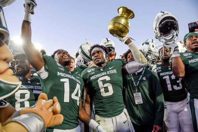 Michigan State's David Dowell holds the Old Brass Spittoon over his head while celebrating the MSUs win over Indiana on Saturday, Sept. 28, 2019, in East Lansing.
