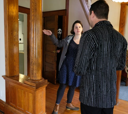 "Abbie Stevens from Lansing, has a few questions for realtor James Pyle about the house she is touring Sunday, Sept. 29, 2019. Dressed as Ghostface from the movie ""Scream"" Andrew Lamkin, peeks out of a closet during the open house. Pyle is surprised by the reaction of viewers as he included the Ghostface character in his Zillow listing which has been viewed by nearly 300,000 people on Sunday. A big Halloween fan he says, ""I just love Halloween and I love putting smiles on peoples faces."""