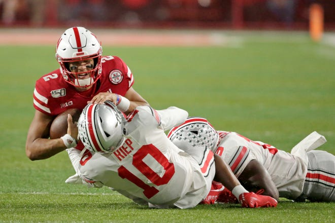 Nebraska quarterback Adrian Martinez is tackled by Ohio State cornerback Amir Riep and linebacker Dallas Gant.