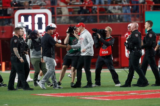 Ohio State's Ryan Day and Nebraska's Scott Frost meet at midfield after Saturday night's game