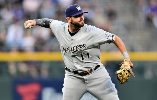 Sep 28, 2019; Denver, CO, USA; Milwaukee Brewers third baseman Mike Moustakas (11) fields the ball in the first inning against the Colorado Rockies at Coors Field. Mandatory Credit: Ron Chenoy-USA TODAY Sports