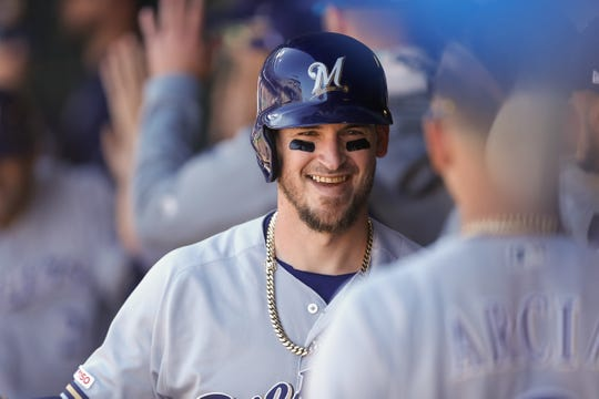 Brewers catcher Yasmani Grandal smiles in the dugout after his two-run homer in the first inning.