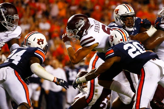 Mississippi State quarterback Garrett Shrader (6) carries the ball for a first down as Auburn defensive backs Jeremiah Dinson (20) and Daniel Thomas (24) defend on Saturday, Sept. 28, 2019, in Auburn, Ala.