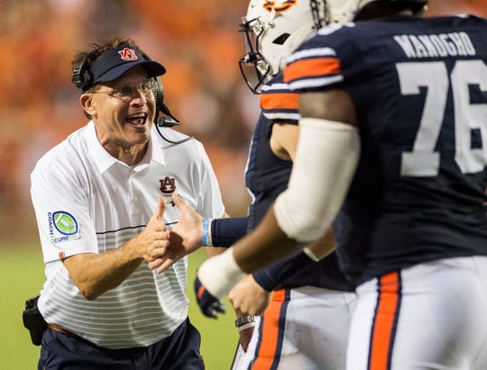 Auburn head coach Gus Malzahn high fives Auburn quarterback Bo Nix (10) after a touchdown pass at Jordan-Hare Stadium in Auburn, Ala., on Saturday, Sept. 28, 2019. Auburn leads Mississippi State 42-9 at halftime.